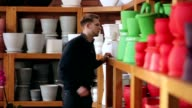 Handsome guy choosing pot for flowers in shop video