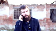 Handsome hipster with beard talking on mobile phone video