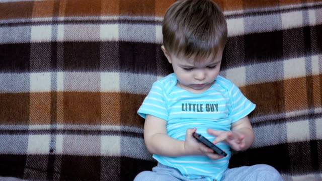 Handsome Little Boy Playing With a Smartphone video