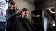 Handsome man doing a haircut for man with black hair at barber shop, modern hair stylist, close up video