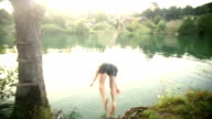 Handsome man doing somersault jump into river video