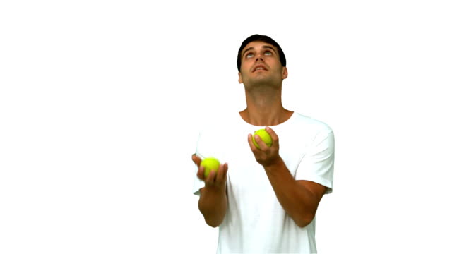 Handsome man dribbling with balls on white screen video