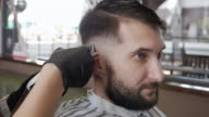 Handsome man getting his head shaved by barber video