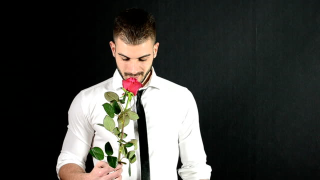 Handsome man giving a red rose video
