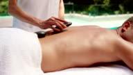 Handsome man having hot stone massage video
