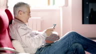 handsome man in jeans and shirt using tablet: web, computer, sofa, sitting, home video