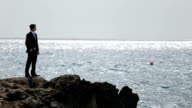 Handsome man in suit standing on the rocky shore and thoughtfully watches the sea waves on back view video