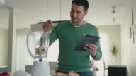 Handsome man is preparing a smoothie while using a tablet computer in the kitchen. video