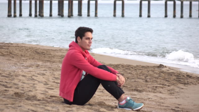 Handsome  man sitting alone at the beach video