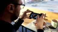 Handsome man talking photo of meal with cellphone sitting in cafe video