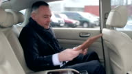 Handsome man using a tablet in the car video