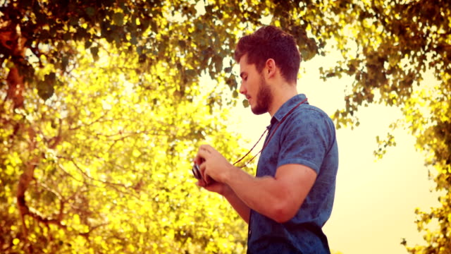 Handsome man using retro photo camera in the park video