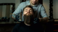 Handsome man with a long beard and undercut in barbershop video