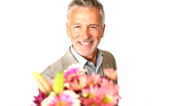 A handsome mature man holding flowers and presenting them to you isolated on white video