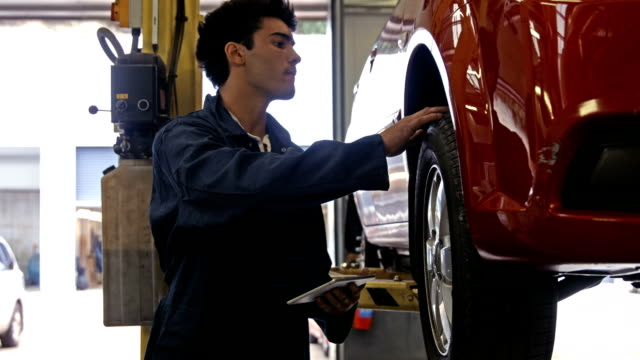 Handsome mechanic overhauling a car video