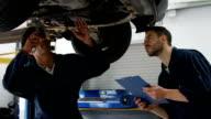 Handsome mechanics overhauling a car video