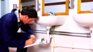 Handsome plumber looking at sink holding clipboard video