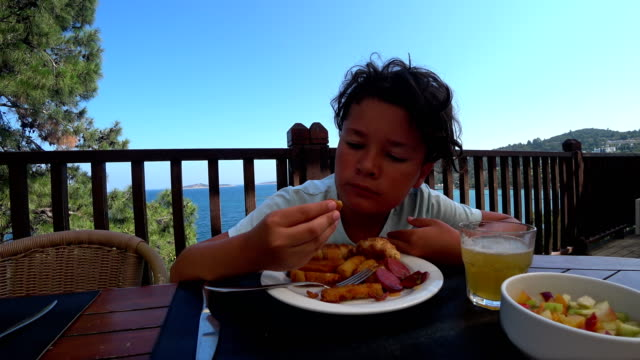 Handsome preteen eating breakfast at the outdoor video