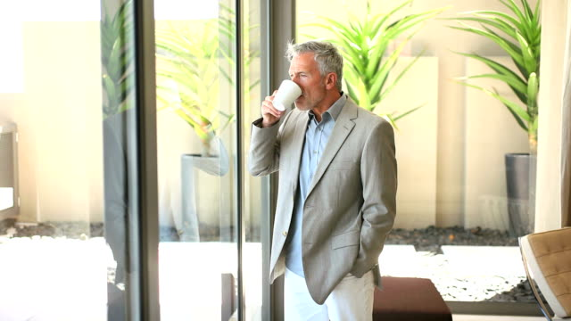 A handsome senior business executive standing by the window having a cup of coffee video