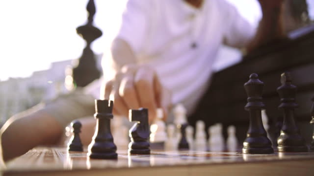 Handsome senior man playing chess outdoors in city, slow motion, close up video