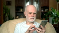 Handsome senior man sitting on chair at home. Using smartwatch, sending message, browsing, reading video