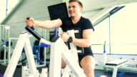 Handsome sporty man is exercising and smiling in fitness club and gym center video