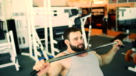 Handsome sporty man is exercising in fitness club and gym center video
