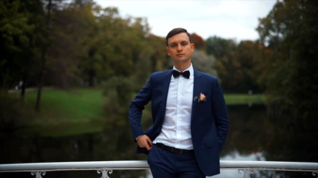 Handsome stylish groom outdoors in park video