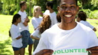 Handsome volunteer showing his tshirt to camera video