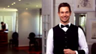 Handsome waiter inviting you inside video