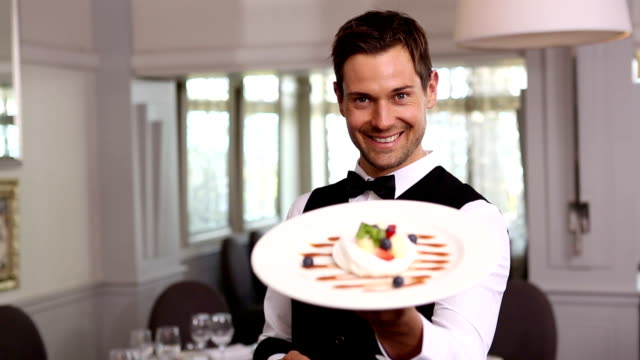 Handsome waiter showing a dessert plate video
