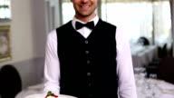 Handsome waiter showing dessert plates video