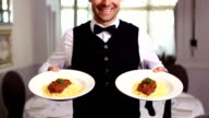 Handsome waiter showing spaghetti dinners video
