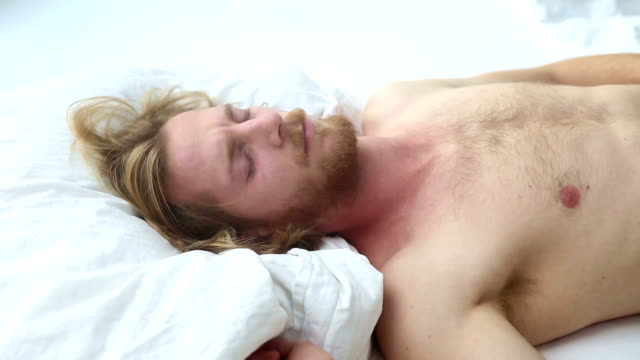 handsome young bearded man waking up in the morning in bed video