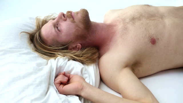 handsome young bearded man waking up in the morning in bed with headache video