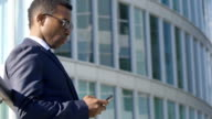 handsome young businessman (African-american) with smartphone video