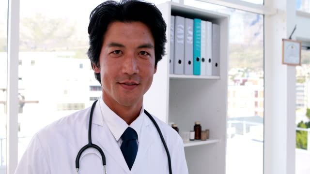 Handsome young doctor smiling at camera video