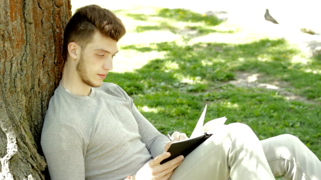 handsome young guy wrote in Notepad under a tree in the Park video