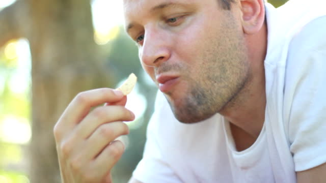 Handsome young man eating chips outdoors video