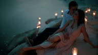 Handsome young man embraces and kisses charming girl in light pink dress while lying on sandy shore with candle lights video