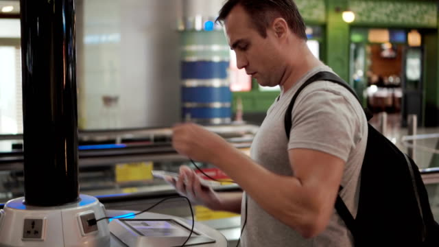 Handsome young man in airport terminal. Standing near charging stand pluging in smartphone video