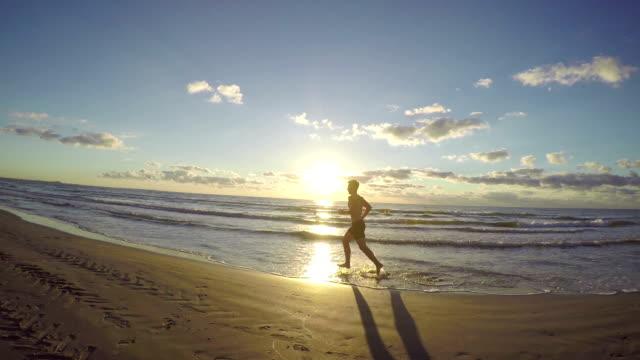 Handsome young man running on wet sandy beach video
