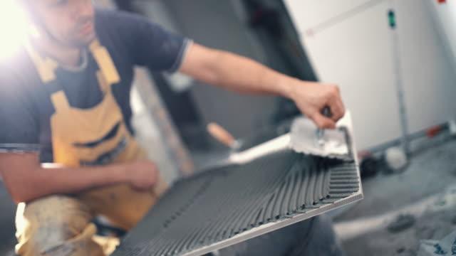 Handyman applying adhesive onto a ceramic tile. video