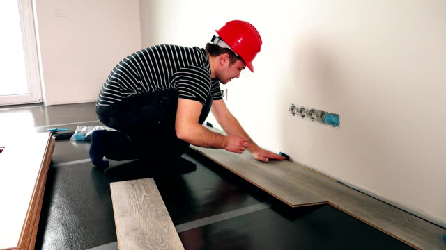 handyman with red helmet installing wooden floor in new house video