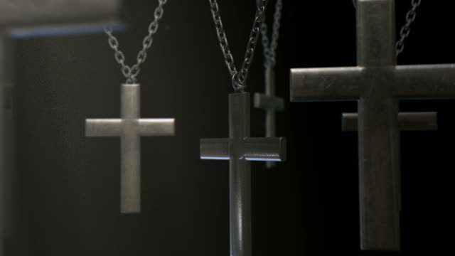 hanging crucifixes and chains spotlight fly through video
