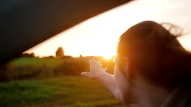 Happiness - young woman in a car, hand playing in the air. Beautiful sunset in the nature. Wind blows hair. Slow mo video