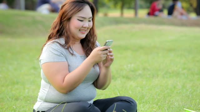 Happy fatty woman using mobile phone video