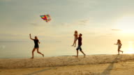 Happy and carefree childhood. Children playing with older kite, running across the sand, laughing video