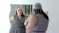happy and vain overweight woman looking herself in the mirror video