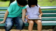 Happy Asian boy and girl Using Wireless Tablet in the park, video